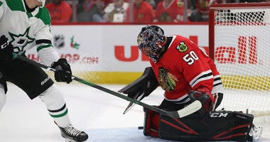 Blackhawks goalie Corey Crawford, right, makes a stop against Stars forward Denis Gurianov.