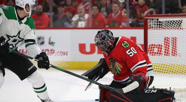 Blackhawks goalie Corey Crawford, right, makes a stop against Stars forward Denis Gurianov.
