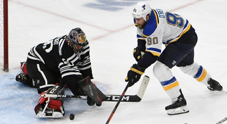 Blackhawks goaltender Corey Crawford (50) makes a save on Blues center Ryan O'Reilly (90).