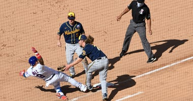 Brewers close Josh Hader tags out Cubs shortstop Javier Baez as Baez tries to slide into first base.