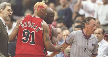 Bulls coach Phil Jackson tries to hold forward Dennis Rodman (91) back as he argues with an official in a playoff game in 1997.