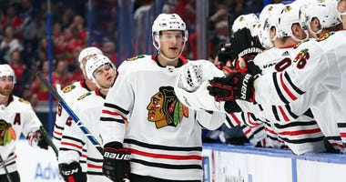 Blackhawks winger Dominik Kubalik (8) is congratulated by teammates after he scores a goal against the Lightning.