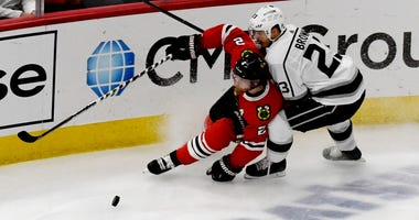 Blackhawks defenseman Duncan Keith (2) and Kings right wing Dustin Brown (23) battle for the puck.