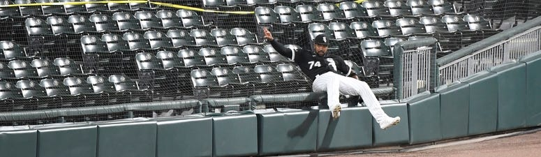 White Sox outfielder Eloy Jimenez (74) falls in the seats attempting to catch a ball against the Brewers.