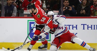 Blackhawks defenseman Erik Gustafsson battles Rangers forward Mika Zibanejad on the boards.