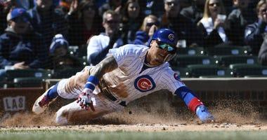 Cubs infielder Javier Baez slides home with a run.