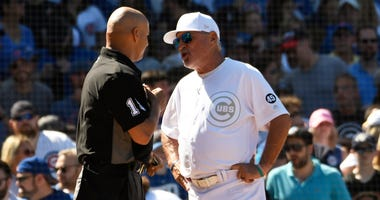 Cubs manager Joe Maddon (70) argues with umpire Vic Carapazza (19).