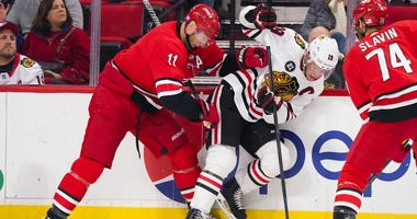 Hurricanes center Jordan Staal (11) and Blackhawks center Jonathan Toews (19) battle for the puck.