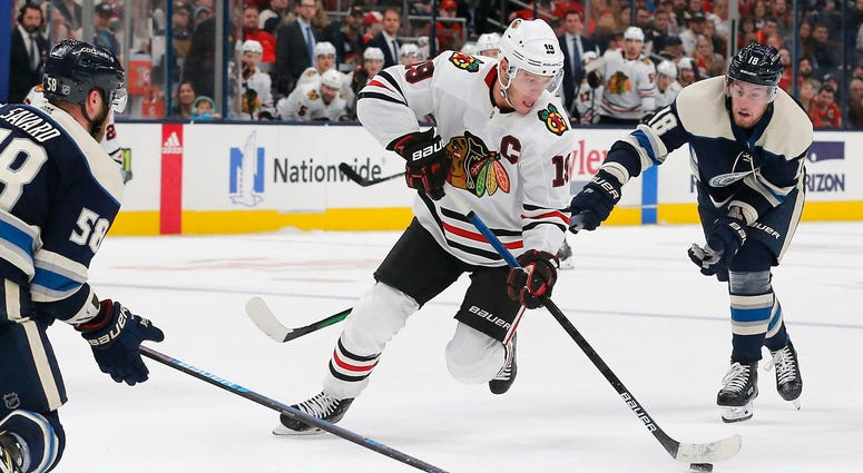 Blackhawks center Jonathan Toews (19) skates past Blue Jackets defenseman David Savard (58).