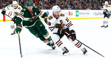 Blackhawks center Jonathan Toews (19) skates with the puck against Wild defenseman Ryan Suter (20).