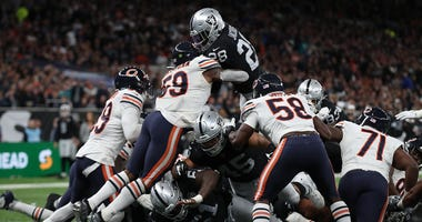 Raiders running back Josh Jacobs leaps over the pile for the winning touchdown against the Bears.