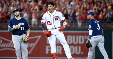 Nationals outfielder Juan Soto celebrate after his single and an error plated three runs against the Brewers in the NL wild-card game.