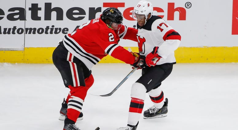 lackhawks defenseman Duncan Keith (2) battles for the puck with Devils right wing Wayne Simmonds (17).
