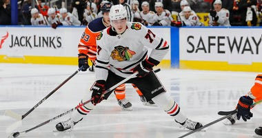 Blackhawks forward Kirby Each (77) tries to get a shot away in front Oilers defenseman Darnell Nurse (25).