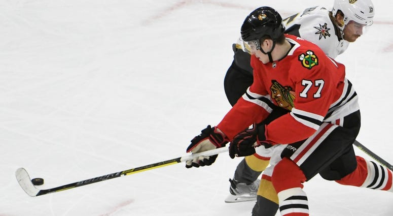 Blackhawks center Kirby Dach (77) tries to get past Golden Knights defenseman Jon Merrill (15).