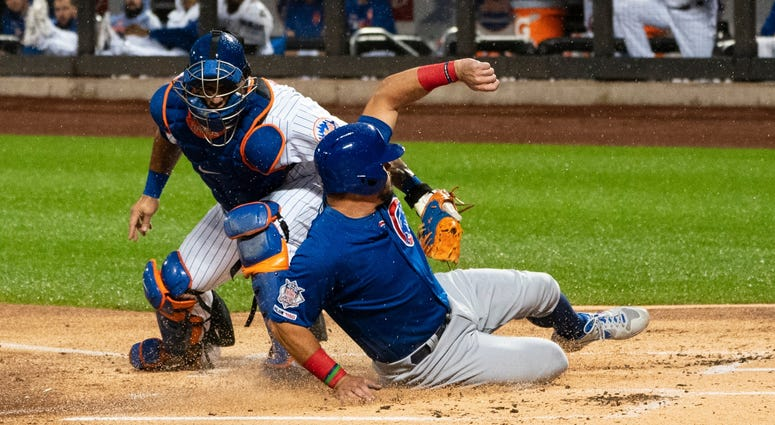 Cubs left fielder Kyle Schwarber (12) slides under the tag by Mets catcher Wilson Ramos (40) and scores a run.