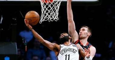 Nets guard Kyrie Irving (11) moves to the basket against Bulls center Luke Kornet (2).