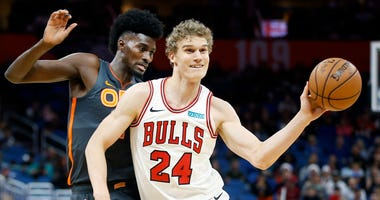 Bulls forward Lauri Markkanen (24) passes the ball in front of Magic forward Jonathan Isaac (1).