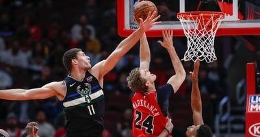 Bulls forward Lauri Markkanen (24) goes to the basket against Bucks center Brook Lopez (11) and forward Giannis Antetokounmpo (34).