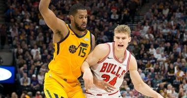 Bulls forward Lauri Markkanen (24) dribbles the ball as Jazz forward Derrick Favors (15) defends.