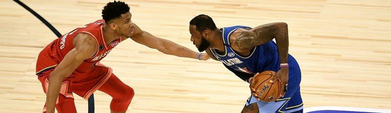 Lakers star LeBron James (right) is guarded by Bucks star Giannis Antetokounmpo in the NBA All-Star Game.