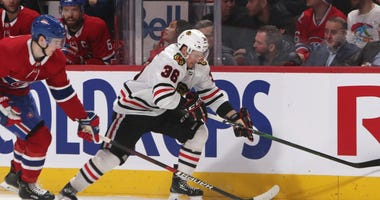 Blackhawks center Matthew Highmore (36) plays the puck against Canadiens defenseman Cale Fleury (20).