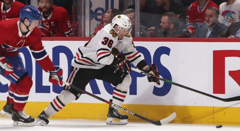Blackhawks center Matthew Highmore (36) plays the puck against Canadiens defenseman Cale Fleury (20).