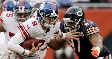 Giants quarterback Daniel Jones scrambles while being pursued by Bears defensive lineman Nick Williams (97).