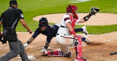 Indians third baseman Jose Ramirez slides home safely past White Sox catcher James McCann to score a run.