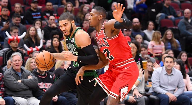 Celtics forward Jayson Tatum (0) drives against Bulls guard Kris Dunn (32).
