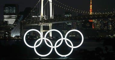 The sun sets behind the Olympic rings at Odaiba Marine Park on March 18, 2020 in Tokyo, Japan.