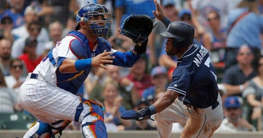 Padres center fielder Manuel Margot (7) comes into score at home plate past Cubs catcher Willson Contreras (40).