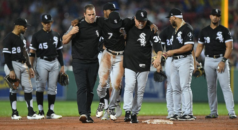 White Sox shortstop Tim Anderson (center) is helped off the after suffering an injury.