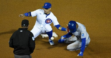 Cubs shortstop Javier Baez catches the ball and applies a tag to record an out against the Royals.