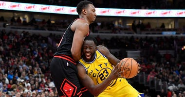 Warriors forward Draymond Green (23) is fouled driving against Bulls center Wendell Carter Jr. (34).
