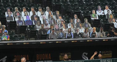 A foul ball heads over the White Sox dugout and toward fan cutouts at Guaranteed Rate Field.