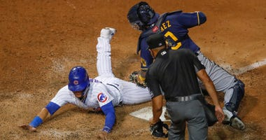 Cubs catcher Willson Contreras (40) slides safely into home plate as a tag from Brewers catcher Omar Narvaez (10) is late.
