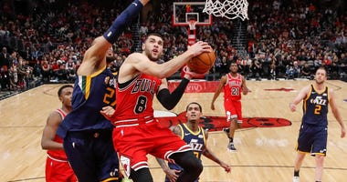 Bulls guard Zach LaVine (8) goes to the basket as Jazz center Rudy Gobert (27) defends.
