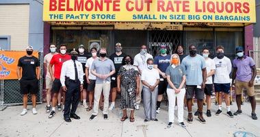 Sam Acho and his group stand outside the liquor store they purchased and are converting into a food mart.