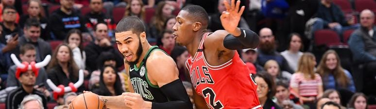 Celtics forward Jayson Tatum (0) drives against Bulls guard Kris Dunn (32).