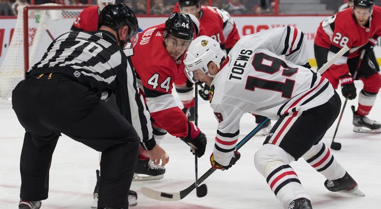 Senators center Jean-Gabriel Pageau (44) faces off against Blackhawks center Jonathan Toews (19).