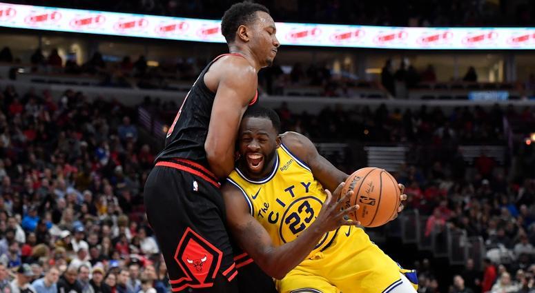 Warriors forward Draymond Green (23) is fouled driving against Bulls center Wendell Carter Jr. (34).