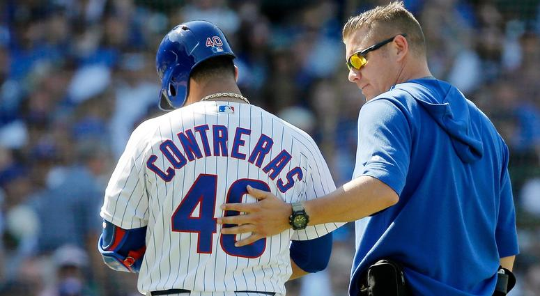 Cubs catcher Willson Contreras (40) walks off the field with head trainer PJ Mainville after suffering a hamstring injury.