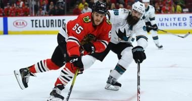 Blackhawks forward Andrew Shaw (65) controls the puck against the Sharks.