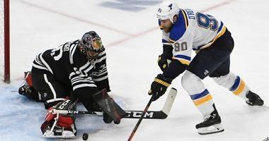 Blackhawks goaltender Corey Crawford (50) makes a save on Blues center Ryan O'Reilly (90).