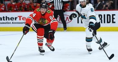 Blackhawks forward David Kampf controls the puck against the Sharks.