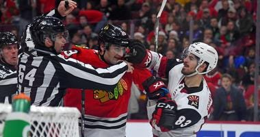 Blackhawks defenseman Dennis Gilbert (39) and Coyotes right wing Conor Garland (83) fight.