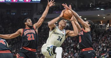 Bucks forward Giannis Antetokounmpo (34) drives for the basket against Chicago Bulls forward Thaddeus Young (21) and guard Coby White (0).