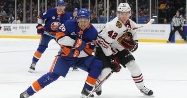 Islanders winger Josh Ho-Sang (26) and Blackhawks defenseman Gustav Forsling (42) fight for a loose puck.