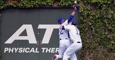 Cubs outfielders Jason Heyward, left, and Kris Bryant collide in a loss to the Reds.